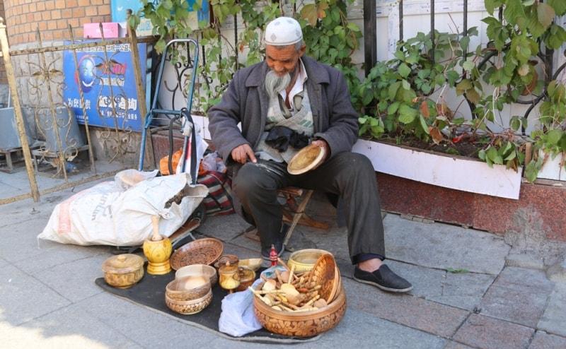 Дедушка больше продает чьи-то изделия, при этом усердно работает и под резчика по дереву.