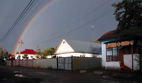 The Local drugstore and a rainbow above settlement.