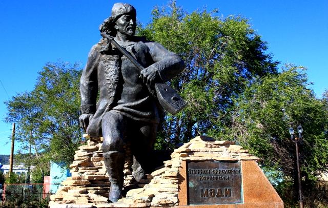 Памятник акыну Мади в центре поселка.