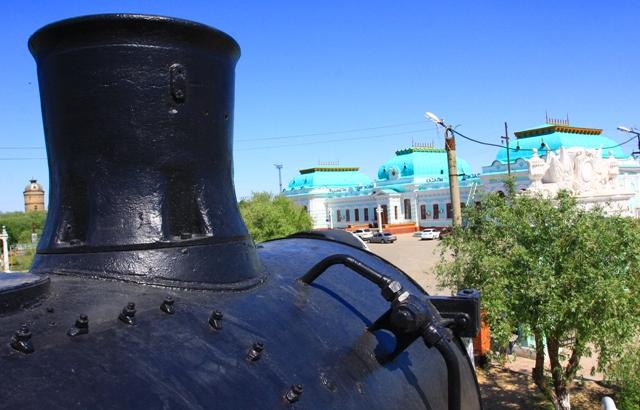Паровозная труба на фоне железнодорожного вокзала в Казалинске.