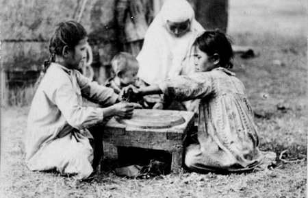 Помол муки вручную. Начало XX века. Фотография Д. Багаева.