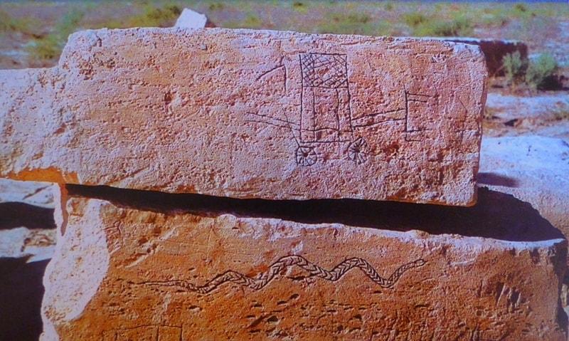 Каменные блоки сарматского храма-святилища Байте III с изображением знаков, рыбы, змеи и повозки.
