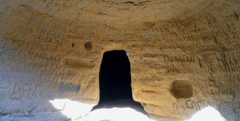 Вход в подземную мечеть Уйтолы, стены исписаны посетителями.