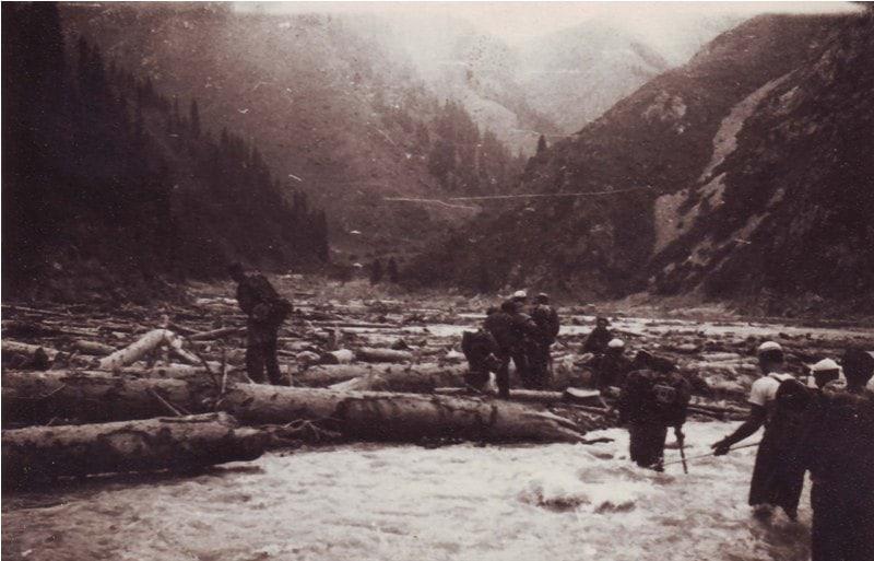 Туристы преодолевают русло реки Иссык, заваленное деревьями, после селя 1963 года. Руководитель Юрий Степанович Накатков. Фотография из семейного архива Накатковых.