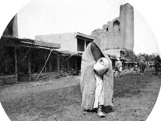 The woman in a veil on a background of mosque Bibu Khanym. Photographer Paul Nadar.